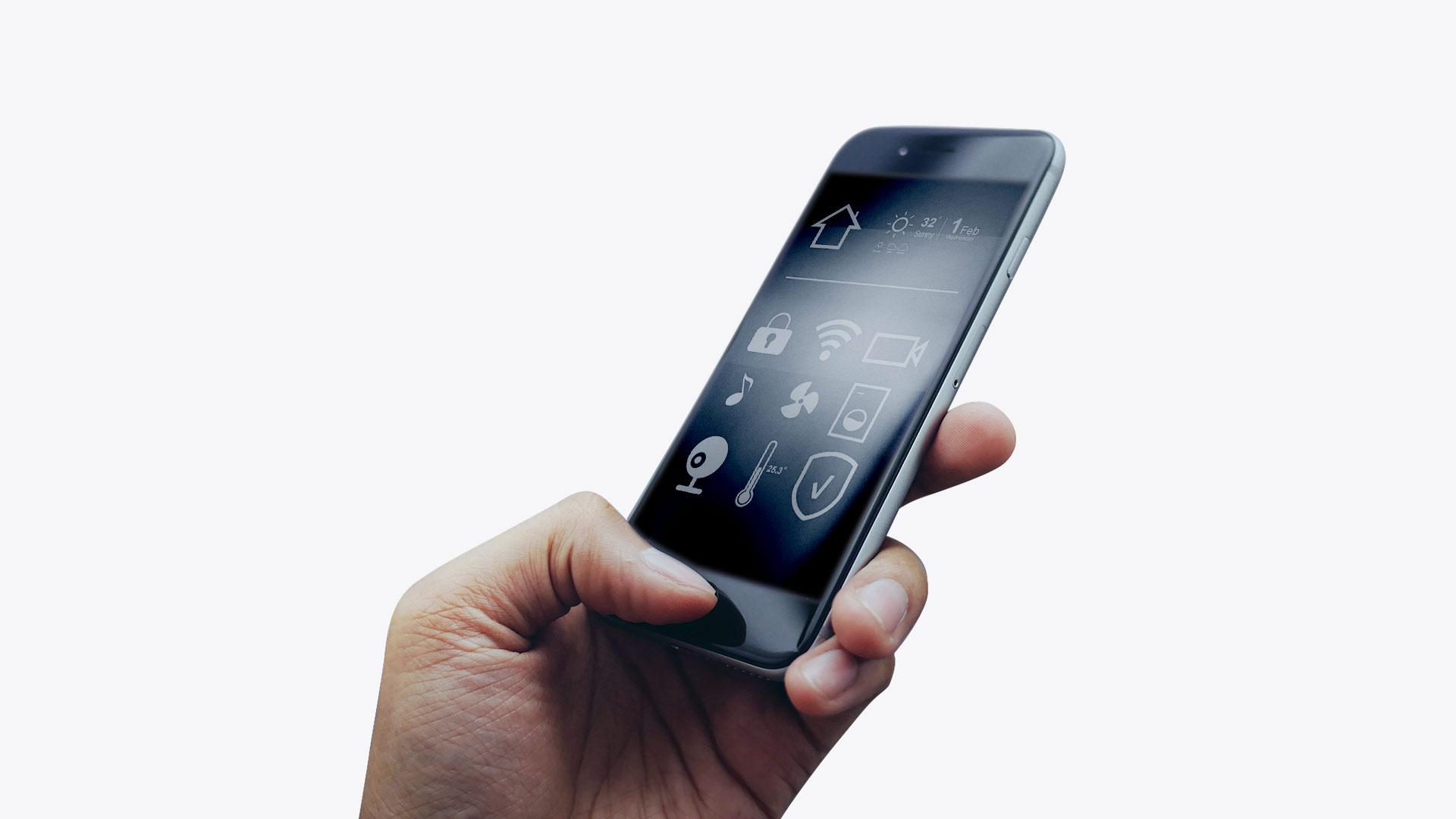 Pametni telefon v roki s sobo v ozadju